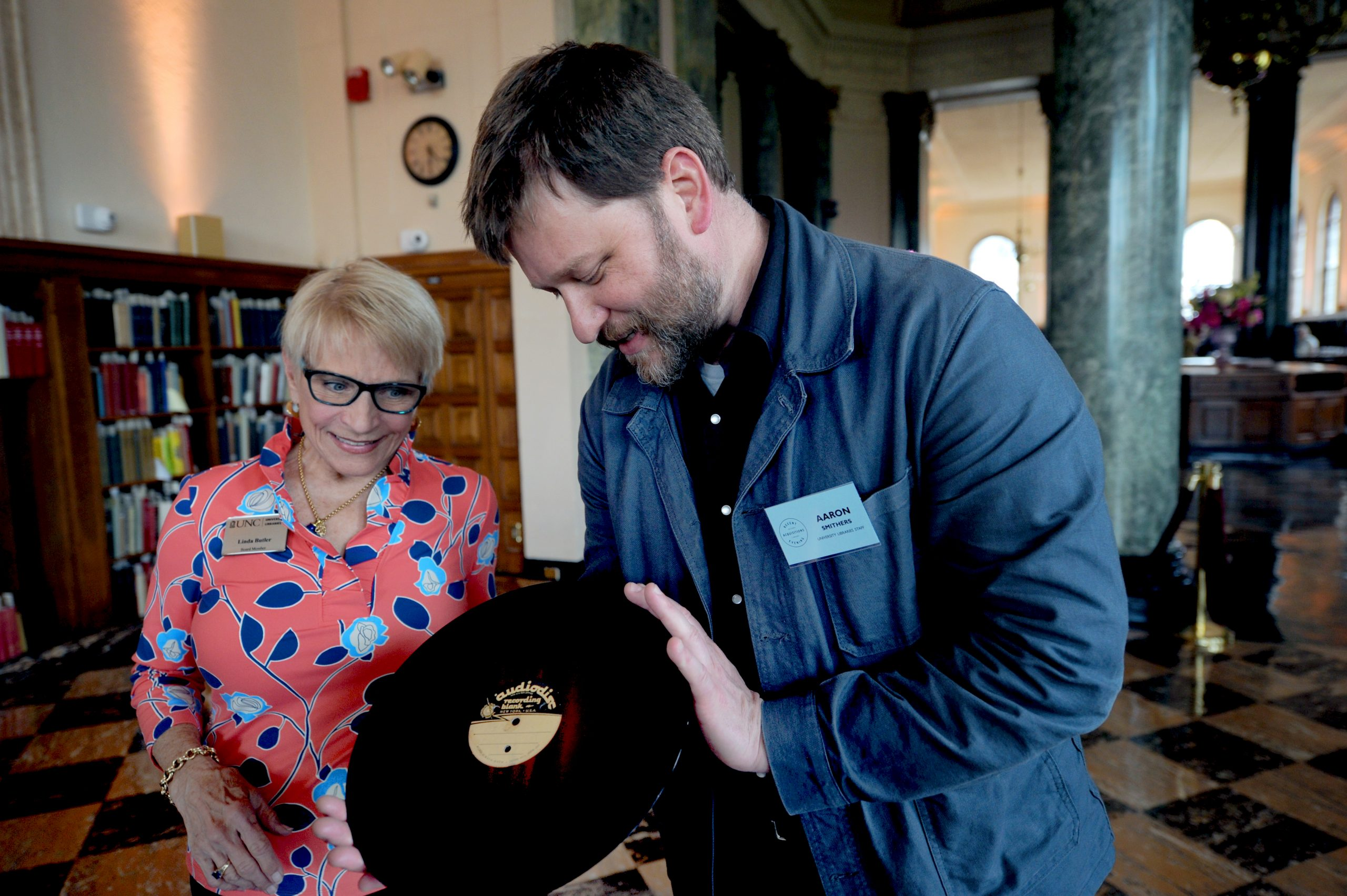 Linda Butler and librarian Aaron Smithers looking at a record.