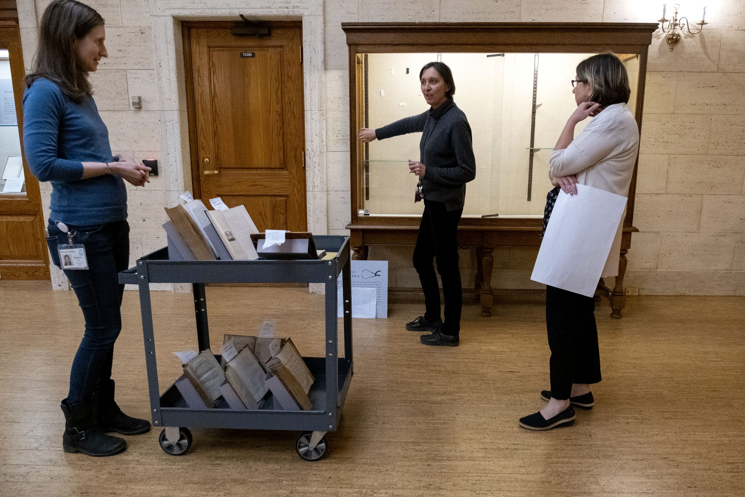 Three women stand in front of a display case with a cart full of books