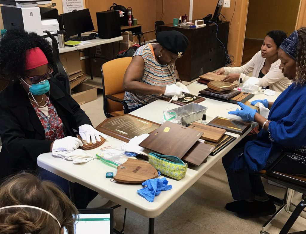 Local HBTSA leaders cleaning museum collections items with CDAT staff on their visit to Hobson City, AL