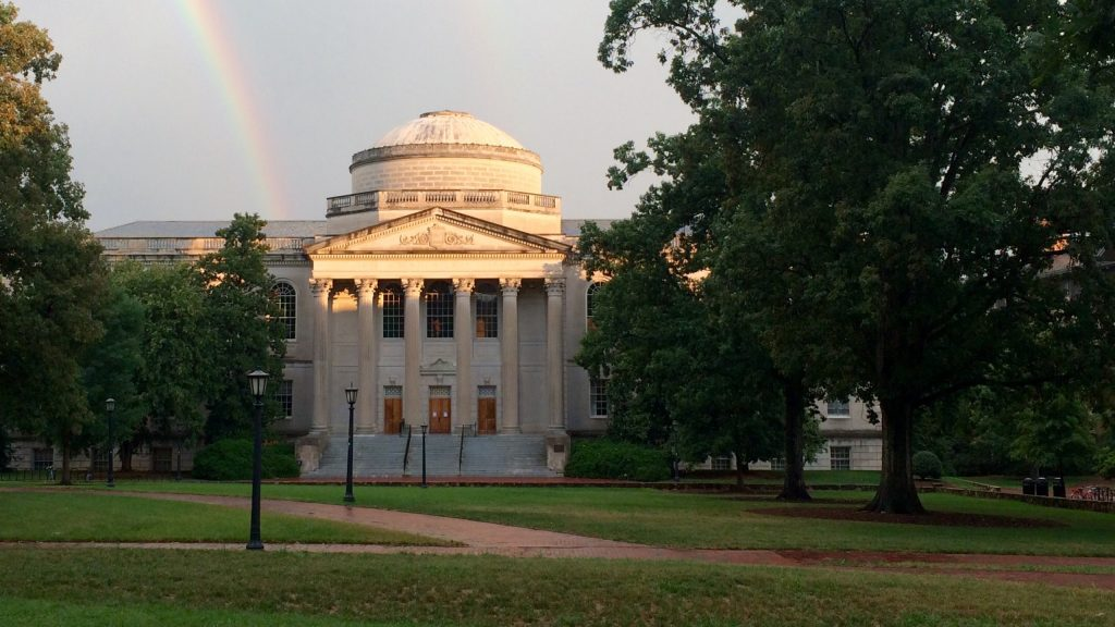 A vew of Wilson library from the quad. A rainbow reaches down to Wilson Library in the sky.