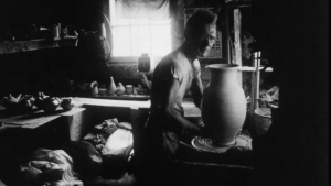 a man at a clay throwing table with a clay vase