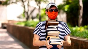 Student carrying a stack of books on campus