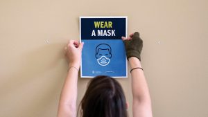 "Library staff person putting a ""wear a mask"" poster on the wall in Davis Library"