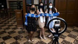 three women in masks and dresses pose for a photo in Wilson