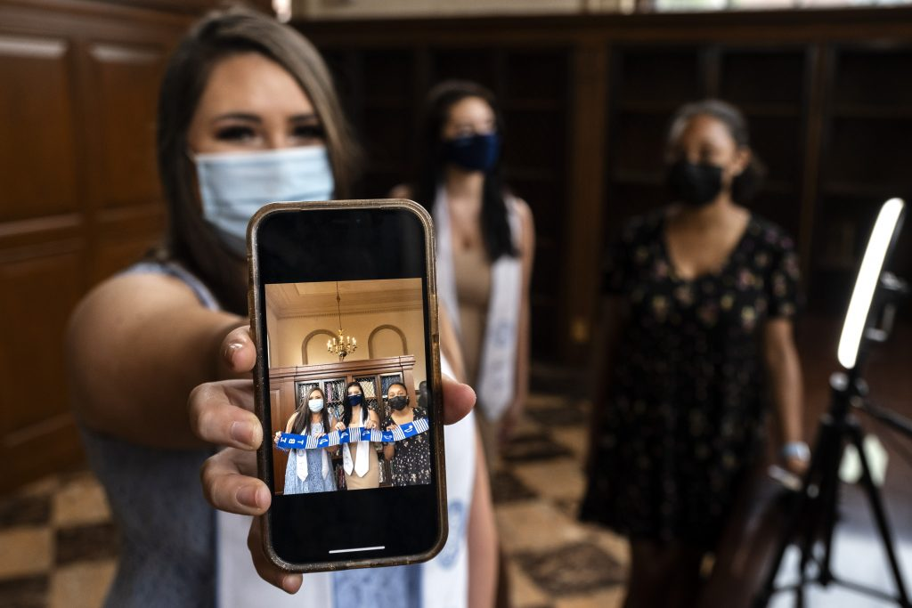 Student showing graduation photo on phone in Wilson Library